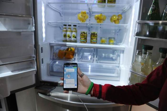 A LG representative shows a smartphone with Home Chat in front of a LG smart refrigerator on the final day of the 2014 International CES, January 10, 2014 in Las Vegas, Nevada. The LG Smart Home system with the Home Chat smart platform allows users to communicate with home appliances via text message.