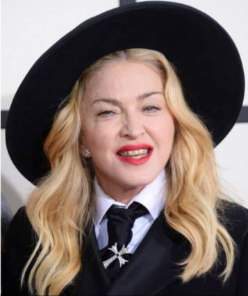Madonna attends Grammys dressed as a witch wearing a Knights Templar (Illuminati) cross pinned to her tie. 1-26-2014