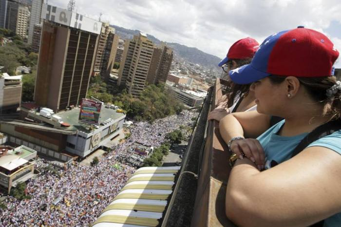 2-23-2014: DISTRESS OF NATIONS: Opposition supporters watch a protest against Nicolas Maduro's government in Caracas February 22, 2014. Venezuela's jailed protest leader urged supporters on Friday to keep demonstrating peacefully against President Nicolas Maduro despite violence that has killed at least six people and rocked the OPEC member nation. (REUTERS/Christian Veron)