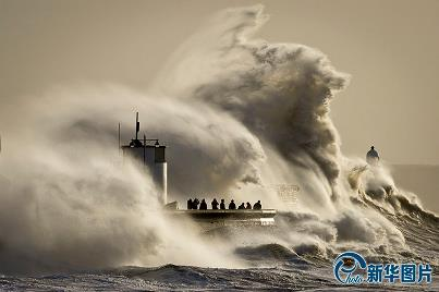 Photo taken on January 6, 2014 shows giant waves hitting South Wales in Britain. Britain has issued flooding warning after a night of rain storms. Weather forecast warned that strong winds and giant waves will strike the west coastline areas.