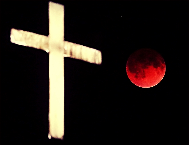 4-15-2014: Lunar Eclipse The Earth's shadow renders the moon in a crimson hue during a total lunar eclipse behind the illuminated steeple of St. Olaf Lutheran Church in the town of Ashippun , Wis. Tuesday, April 15, 2014. (AP Photo/Wisconsin State Journal, John Hart)