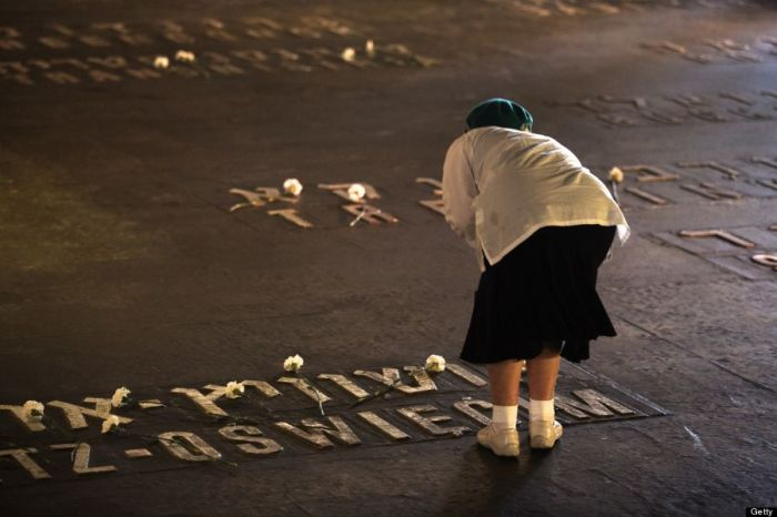 4-28-2014: A relative of Holocaust victims lays flowers on the names of concentration camps in the hall of remembrance at the Yad Vashem Holocaust Memorial on April 28, 2014 during the Holocaust memorial day in Jerusalem. (MENAHEM KAHANA/AFP/Getty Images)