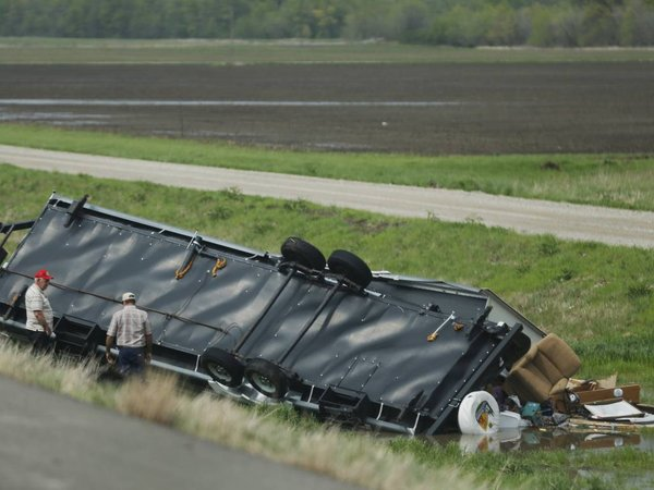 4-27-2014: Motorists check out a travel trailer damaged in an accident involving high winds from a severe thunderstorm that passed near Rich Hill, Mo., Sunday. (AP Photo/Orlin Wagner)
