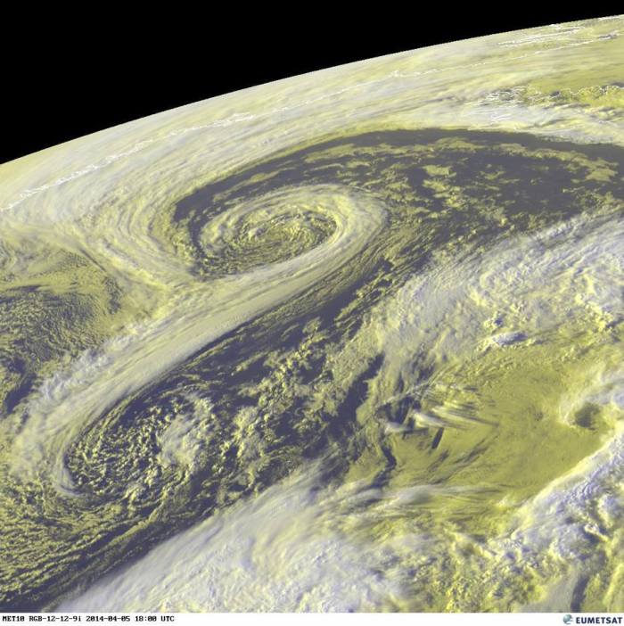 4-5-2014: Spectacular evening view of twin cyclones in the northern Atlantic, south of Iceland. The deeper northern cyclone, with a spectacularly developed vortex structure is at current central MSLP of 972 mbar. It will remain almost stationary over the next 12-18h, moving only slightly to the NW. The southern, shallower cyclone will move NE and bring gale force winds south Ireland in the morning hours. Source: EUMETSAT