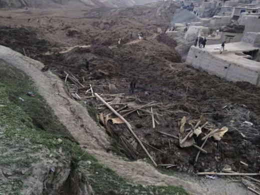 5-2-2014: Afghan villagers gather at the site of a landslide at the Argo district in Badakhshan province,