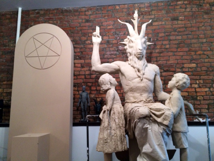 """In January the Satanic Temple announced plans to erect a monument glorifying the Dark Lord on the front lawn of the Oklahoma Statehouse. An Indiegogo campaign was launched with what seemed like a somewhat lofty goal of $20,000, but by the time donations ended almost $30,000 had been raised. Now an artist trained in classical sculpture is toiling away in New York, crafting a Baphomet figure sitting beneath an inverted pentagram and flanked by two children gazing upward in loyalty. When it is finished, it will be cast in bronze and, the Satanists hope, eventually displayed in Oklahoma."""