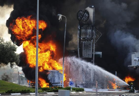 Israeli firefighters extinguish a fire that broke out after a rocket hit a petrol station in the southern Israeli city of Ashdod July 11, 2014. REUTERS/Avi Roccah