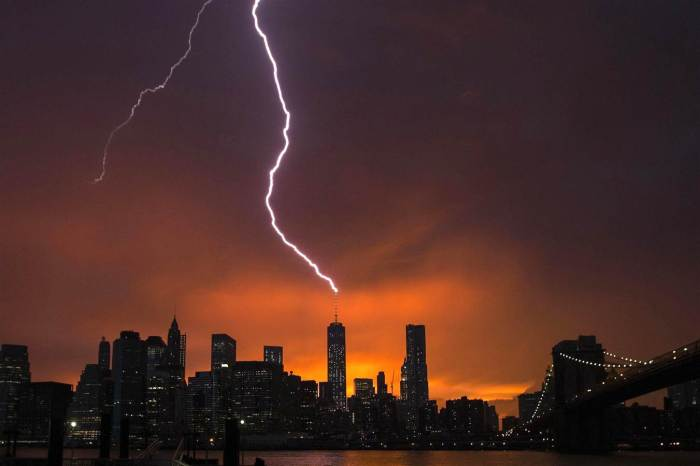 7-2-2014: Lightning strikes One World Trade Center in Manhattan as the sun sets behind the city after a summer storm in New York.