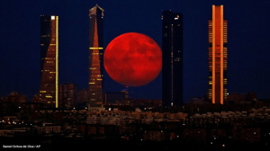 The moon rises in the sky as seen through the Four Towers, or Cuatro Torres Business Area, in Madrid, Spain on Aug. 11, 2014.