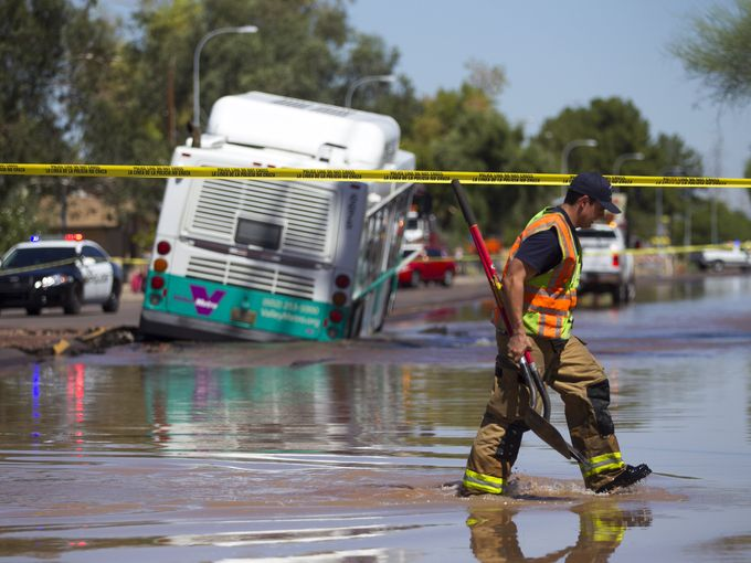9-4-2014: Arizona - ​Tempe officials used a crane to pull a bus out of a sinkhole after a water main broke Wednesday morning near Apache Boulevard and McClintock Drive.