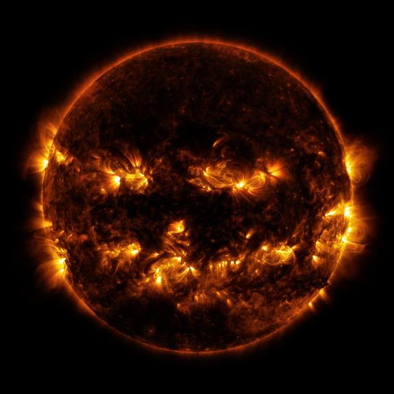 "NASA's Solar Dynamics Observatory (SDO) snapped the composite photo as the spacecraft stared at the sun from its spot in space on Oct. 8, 2014. In the image, hotspots of magnetic fields on the sun have gathered to form what appears to be two ""eyes,"" a nose and a super-spooky grin on the sun's face. There even appear to be ears on the sides of the sun. The image is a composite of two taken in extreme ultraviolet light. Active regions on the sun, which include magnetic activity in the sun's atmosphere (corona), shine brighter and created the jack-o-lantern-like face."
