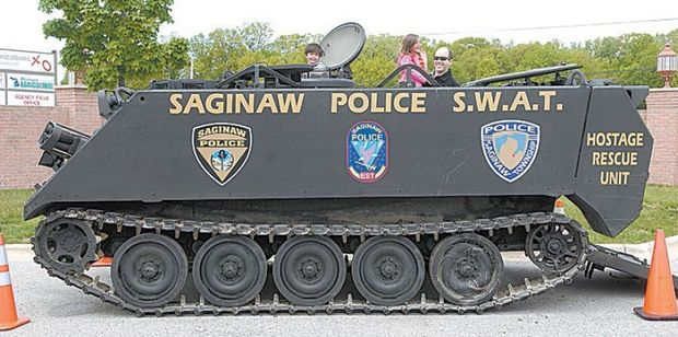 Michigan - Tim Brown, 35, holds daughter Drea, 4, as son Dean, 2 1/2, right, checks out the view from the hatch of the Saginaw Police Department's armored personnel carrier during the EMS Week kick-off at Saginaw Valley Medical Control Authority on Tittabawassee in May 2008.