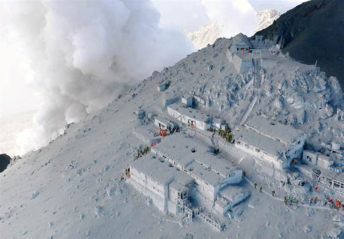 Firefighters and members of Japan's Self-Defense Forces conduct a rescue operation at a cabin near the peak of Mount Ontake as plumes of smoke billow in central Japan, on Sept. 28, 2014. Mount Ontake erupted shortly before noon Saturday, spewing large white plumes of gas and ash high into the sky and blanketing the surrounding area in ash. Rescue workers on Sunday found more than 30 people unconscious and believed to be dead near the peak of an erupting volcano, a Japanese police official said.
